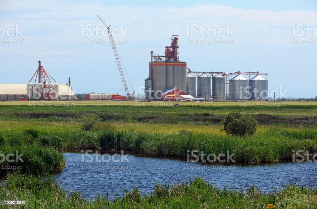 Prairie Grain Elevator Landscape With Water In Foreground stock photo