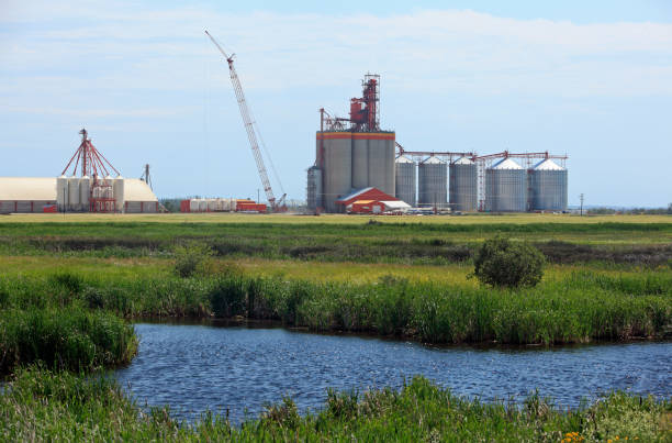 Paysage de silos à Grain des Prairies avec de l'eau au premier plan - Photo