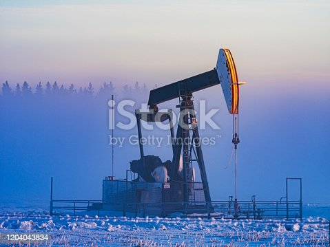 oil pumping in winter morning, alberta, canada.