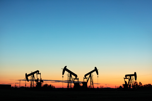 Four pump jacks producing oil, Image taken near the town of Virden, Manitoba. Image taken from a tripod.