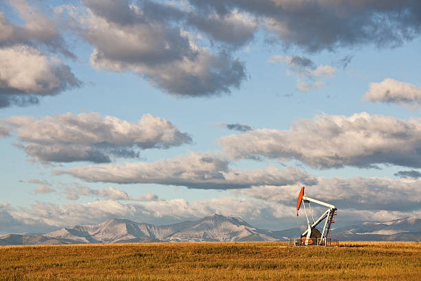 Prairie Pumpjack in Alberta Canada A pumpjack on the prairie. Alberta, Canada.Rocky Mountains in distance. Crude oil and the oil industry in general is a huge industry in Western Canada. Additional themes here include natural gas, fossil fuel, energy, gas, power, scenic, landscape, oil field, oilsands, pipeline, oil rig, geology, engineering, and fracking.  alberta stock pictures, royalty-free photos & images