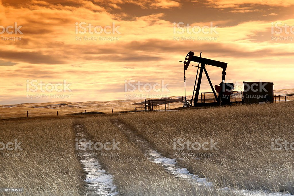 Prairie Pumpjack with Dramatic Sunset Sky royalty-free stock photo