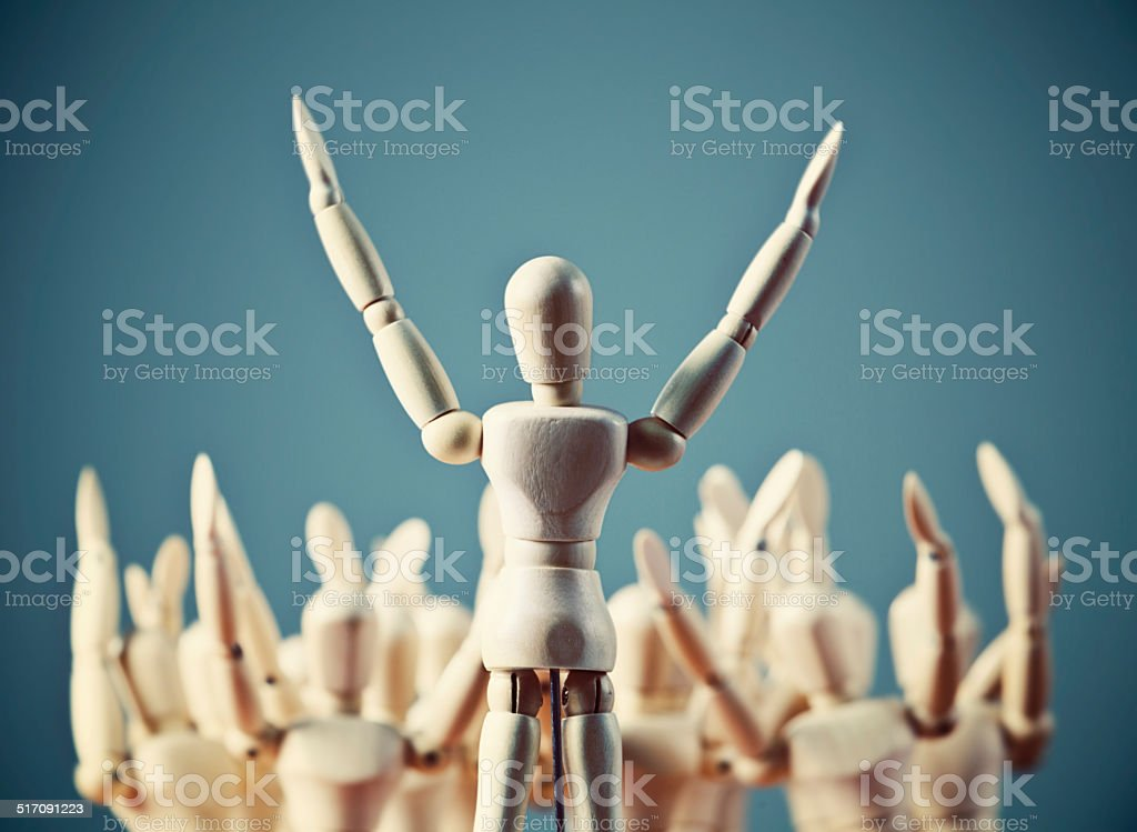 Praise the Lord! Enthusiastic puppet preacher leads crowd of faithful stock photo