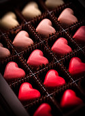 Pralines assortment group heart shaped closeup gradually colored in luxury brown box package