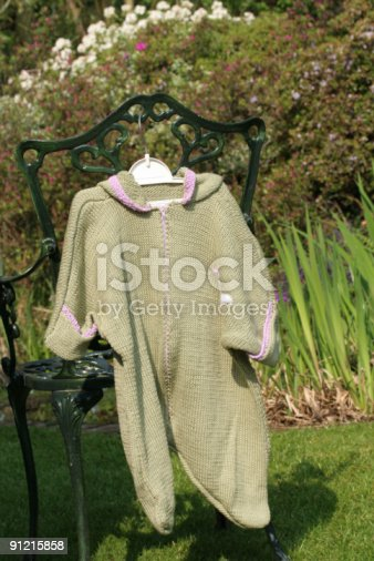 A baby's hand knitted pram suit hanging on the back of an old garden chair.