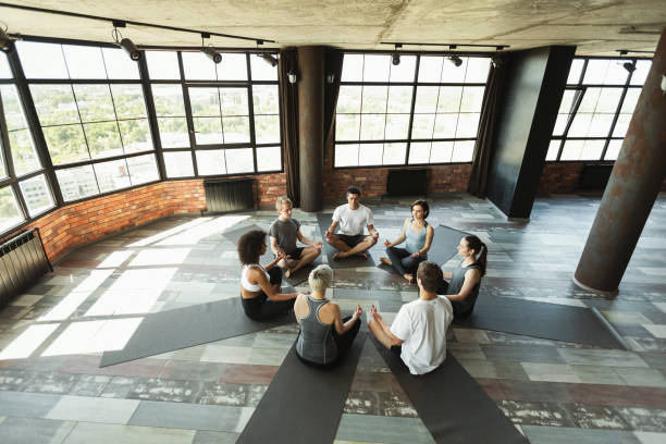 Pranayama in yoga class, aerial view Diverse young people sitting on mats in circle doing breathing practice, yoga studio in loft, aerial view. yoga class stock pictures, royalty-free photos & images