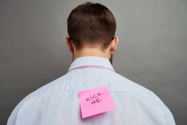 Pranked man Rear view of man with note on his back april fools day stock pictures, royalty-free photos & images