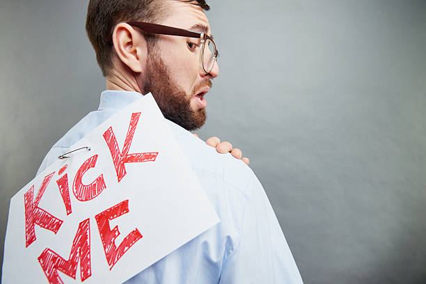 Pranked nerd Office worker with kick me sign on his back april fools day stock pictures, royalty-free photos & images