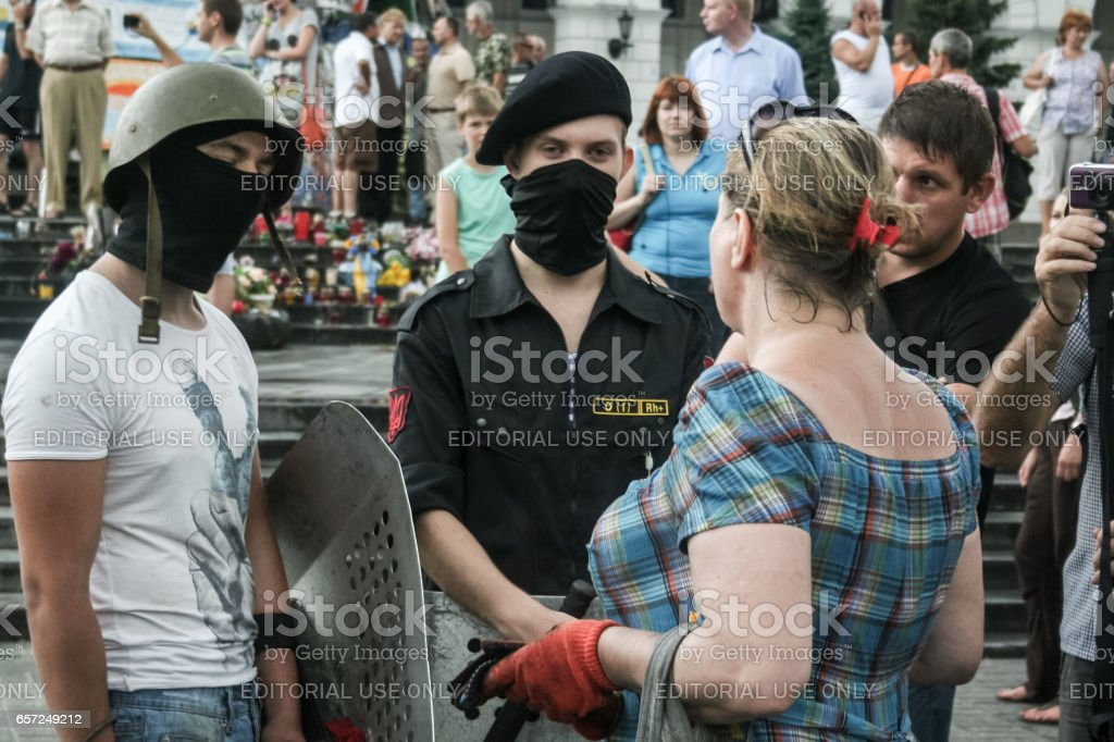 Kiev, Ukraine - August 9, 2014: Pravy Sektor Military volunteer observing the removal of the last barricades on Maidan Square (independence Square) in Kiev stock photo