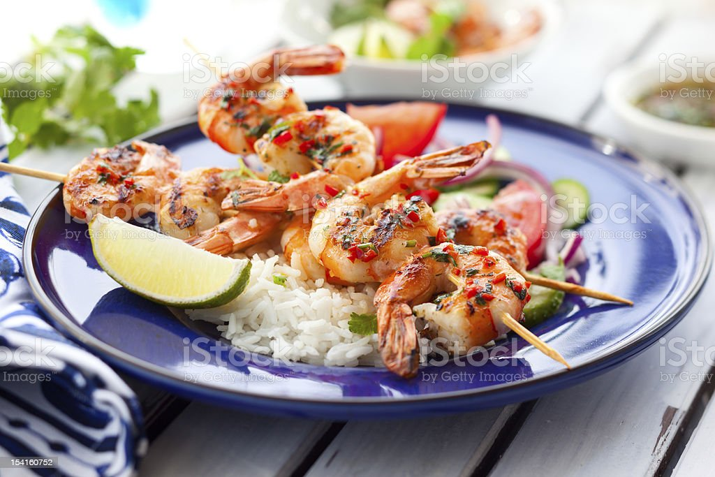 Prawn skewers on a bed of rice with a lime garnish royalty-free stock photo