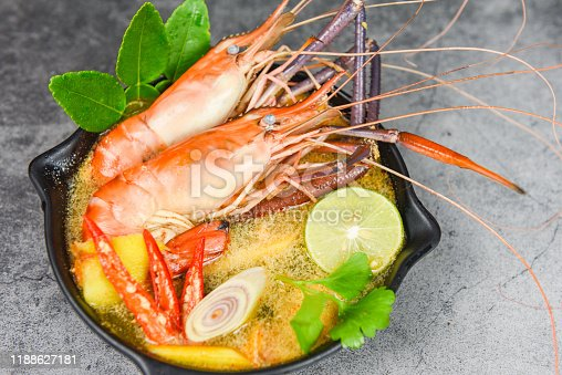 Prawn spicy soup bowl with spices ingredients on dark background / Cooked seafood with shrimp soup dinner table thai food asian traditional , Tom Yum Kung