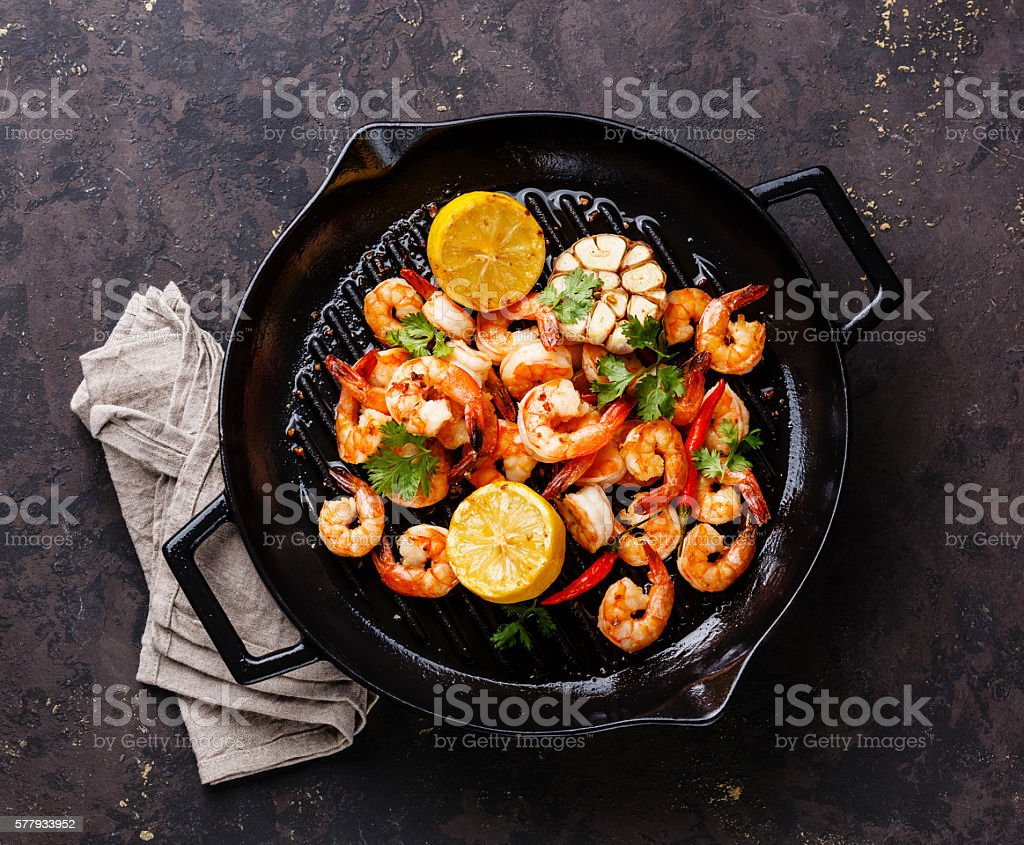 Prawns frying pan with lemon and garlic stock photo