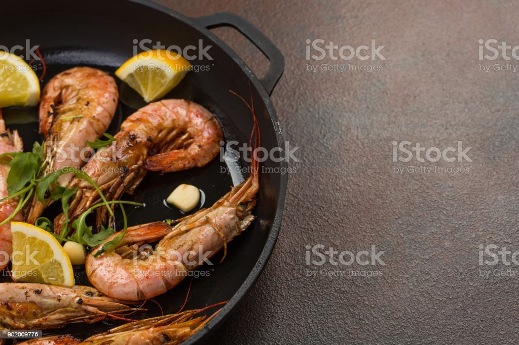 prawns shrimps with garlic, lemon, spices and italian parsley garnish in a black pan on white painted rustic wood, selected focus, narrow depth of field stock photo