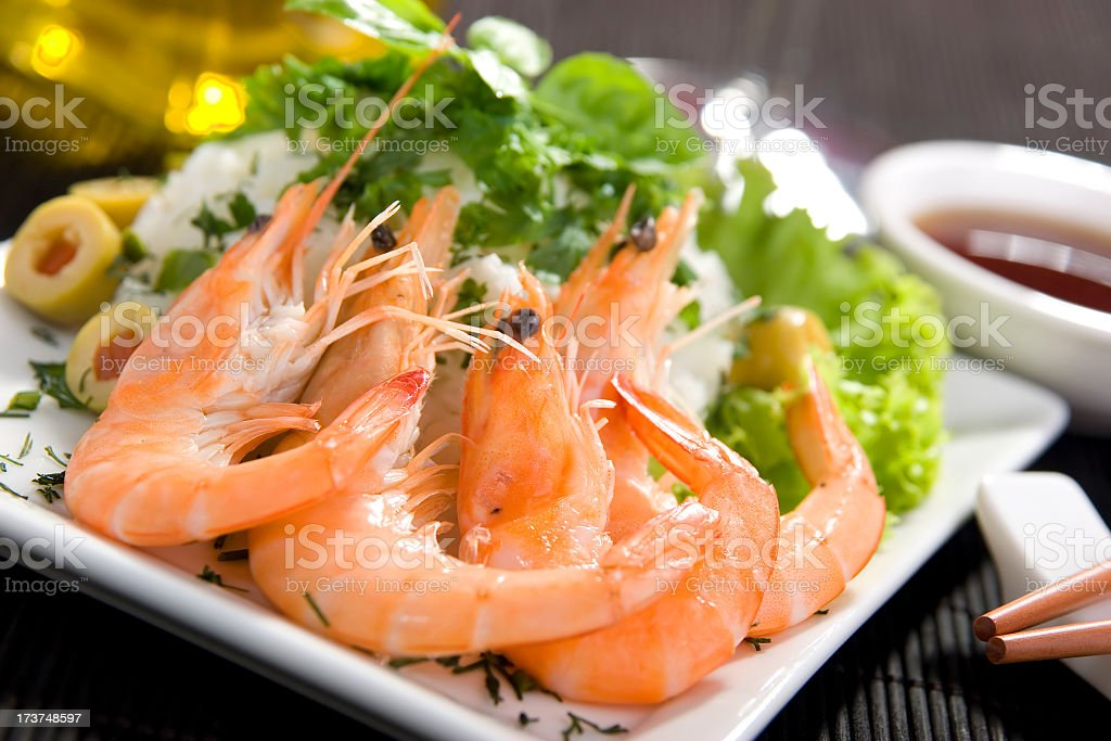 Prawns with their heads on are on a plate with garnish royalty-free stock photo