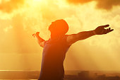 Silhouette of man praying and feel free with heavenly cloudscape sunset concept for religion, worship, love and spirituality