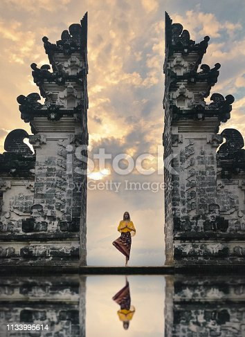 Girl is standing in the gate of Pura Lempuyang temple on Bali island