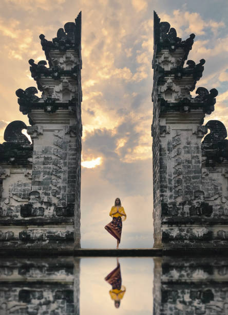 Pray Girl is standing in the gate of Pura Lempuyang temple on Bali island indonesia stock pictures, royalty-free photos & images
