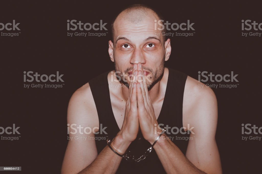 Prayer. Arrested criminal man with handcuffs on his hands pray to God. Isolated on black background. royalty-free stock photo