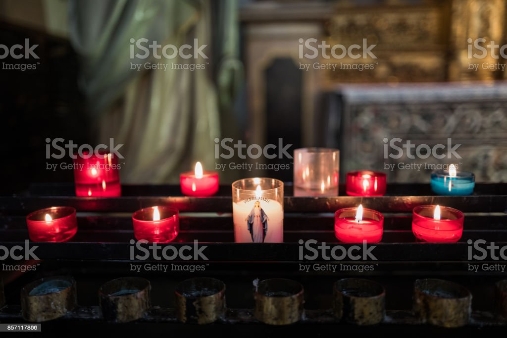 Prayer Candles in Church with Virgin Mary stock photo