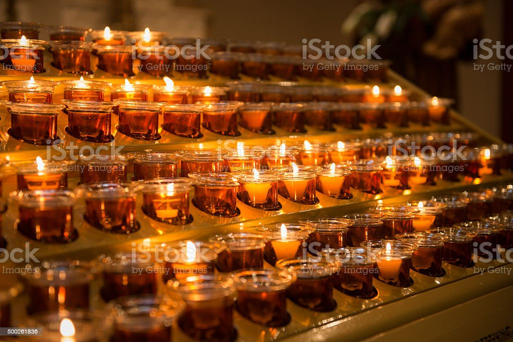 Prayer candles light up the darkness in a church stock photo