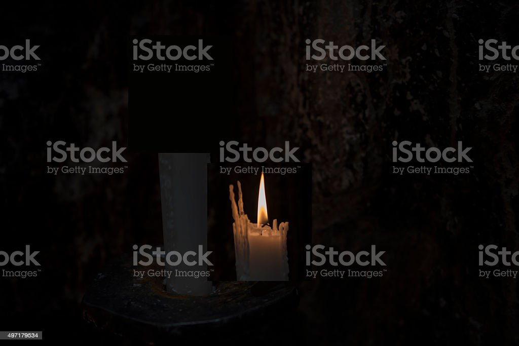 Prayer candles light up the darkness stock photo