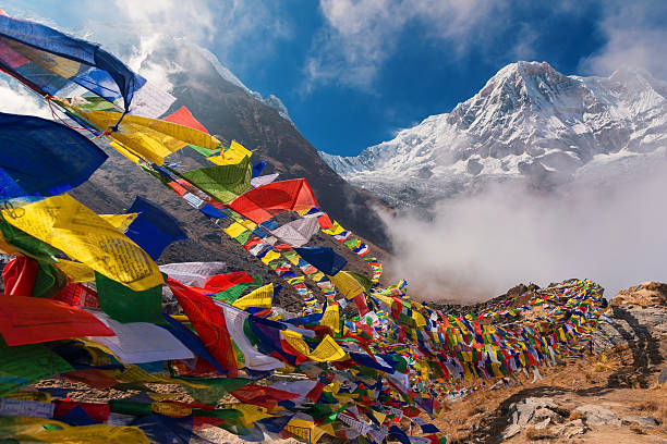 prayer flags and mt. annapurna i background - népal photos et images de collection