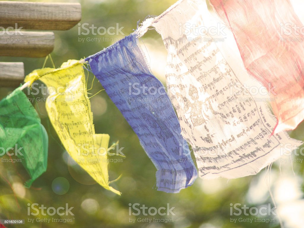 Prayer Flags Fluttering Gently in the Sun Lens Flare Bokeh stock photo