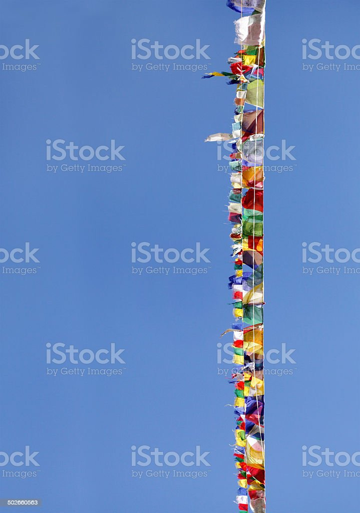 Prayer flags of different colors on blue sky stock photo
