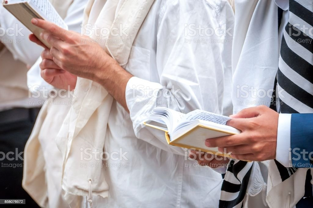 Prayer. Hasid in traditional clothes. Tallith - jewish prayer shawl. Hands hold a prayer book. Close-up. stock photo