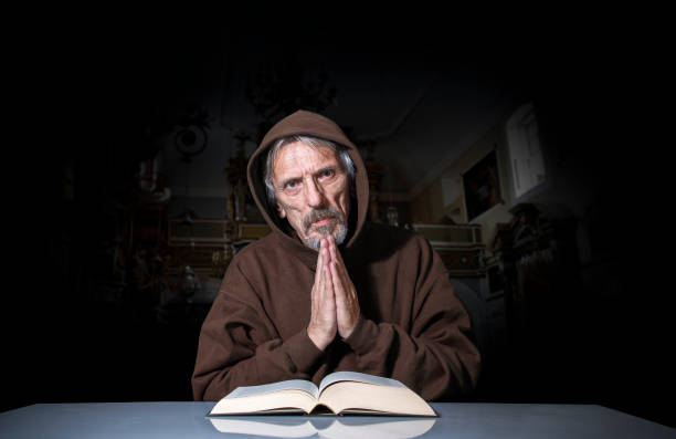 Prayer The man praying in the church. friar stock pictures, royalty-free photos & images