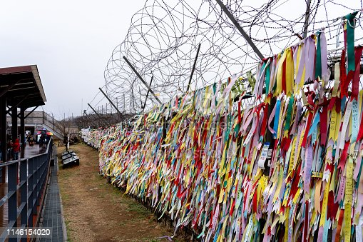 Paju, South Korean - April 10, 2019: Prayer ribbons tied on the fence at Imjingak Park near DMZ in Paju, South Korea. South Koreans tie ribbons with messages for their family members in the North.