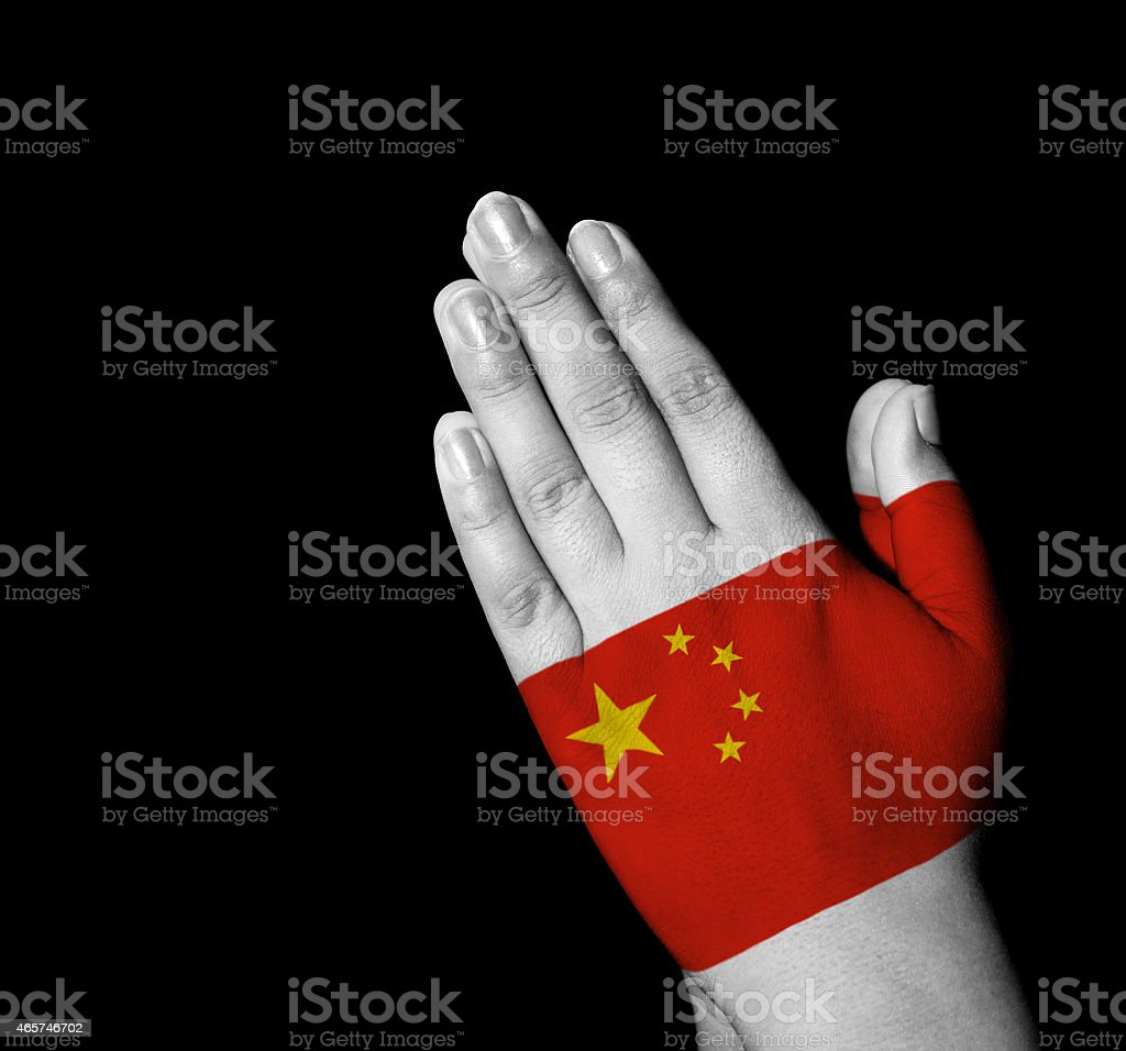 Prayer - The-People's-Republic-of-China flag painted on hands stock photo