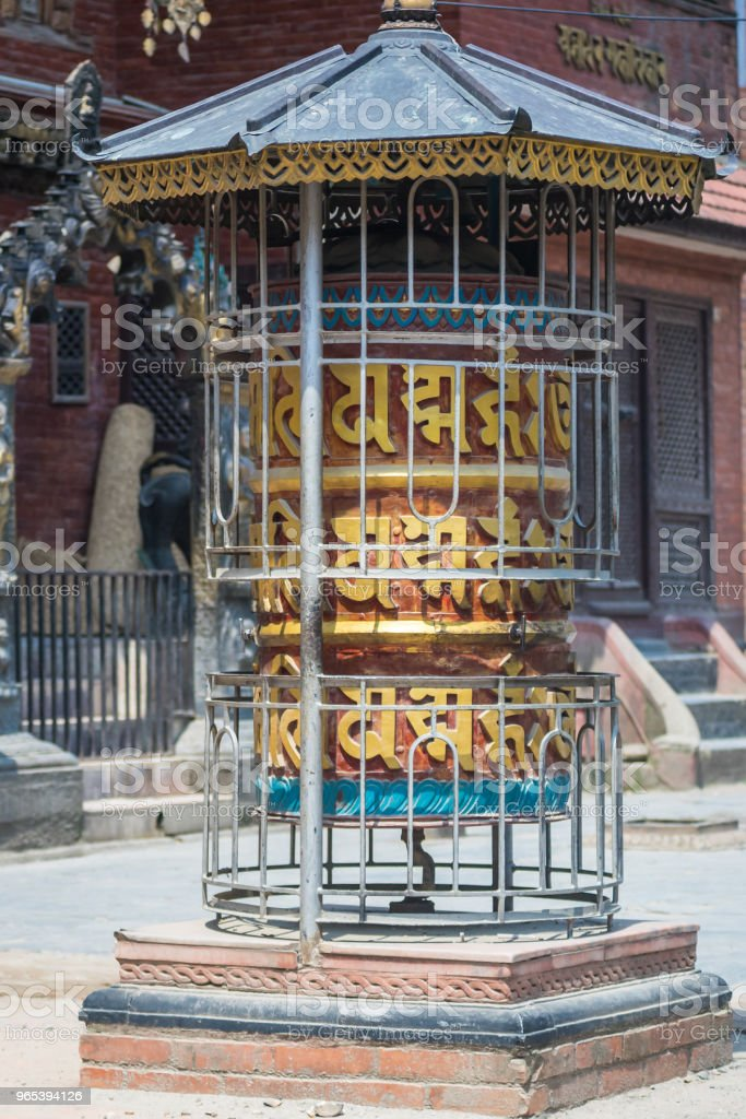 Prayer wheel in front of temple in Nepal royalty-free stock photo
