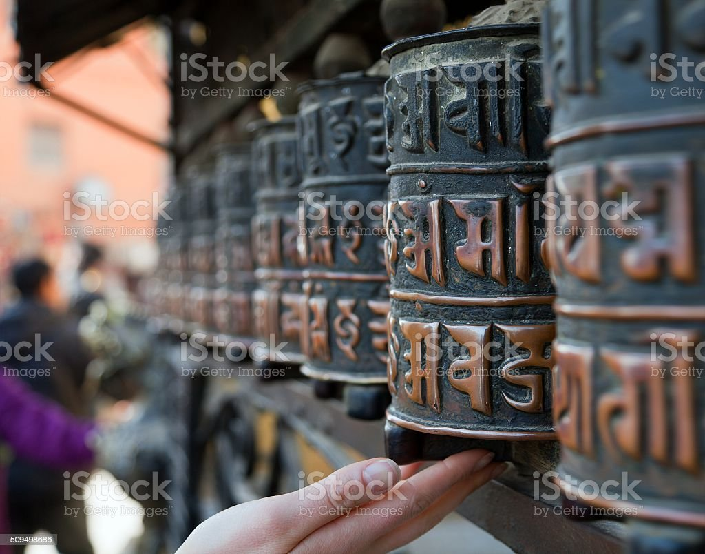 Prayer wheels and hand stock photo