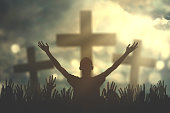 Silhouette of christian prayers raising hand while praying to the GOD with three cross symbols