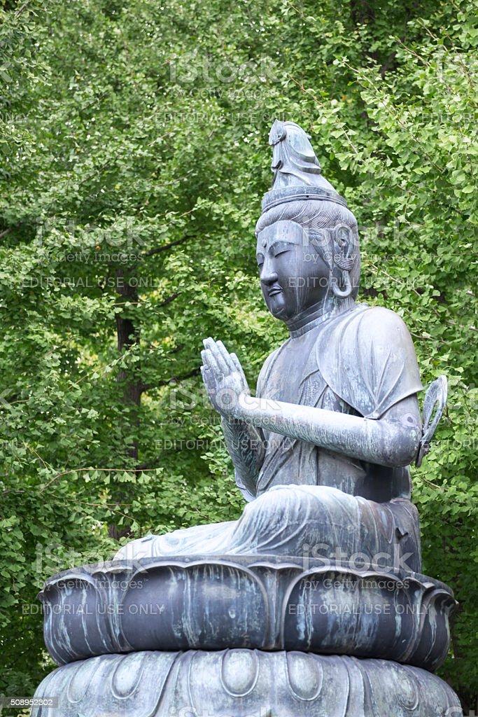 Praying Buddha sitting in lotus postion on lotus flower royalty-free stock photo