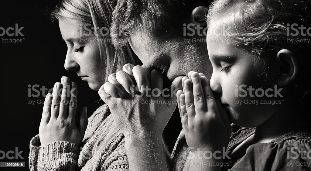 Praying family. Man, woman and child. stock photo