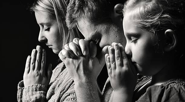 Praying family. Man, woman and child. stock photo