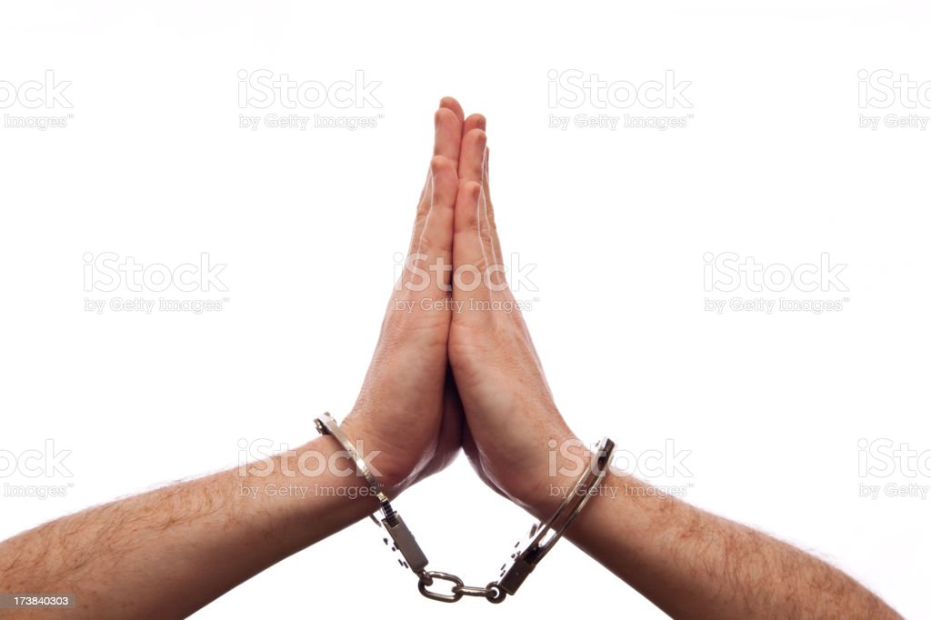 Praying hands in handcuffs isolated on white A pair of hands adopts a prayerful pose while handcuffed, isolated on a white background.  2000-2009 Stock Photo