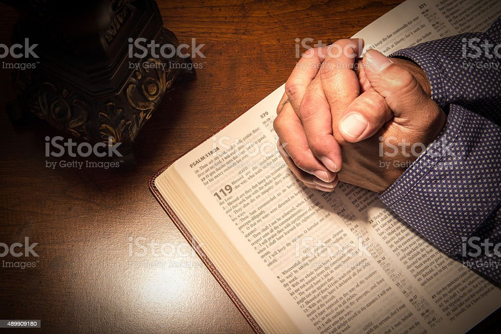 Praying hands on a bible stock photo