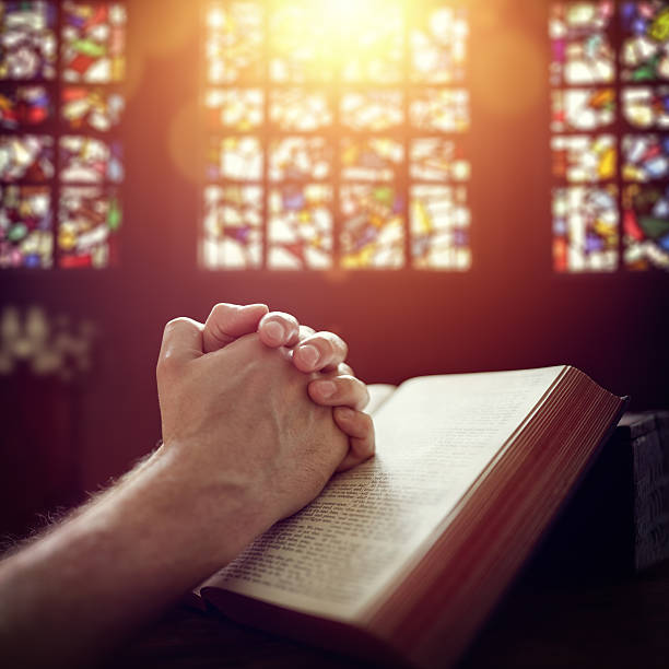 praying hands on a holy bible - catholicism stock photos and pictures