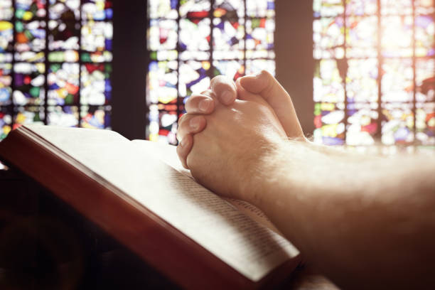 praying hands on a holy bible - preacher stock photos and pictures