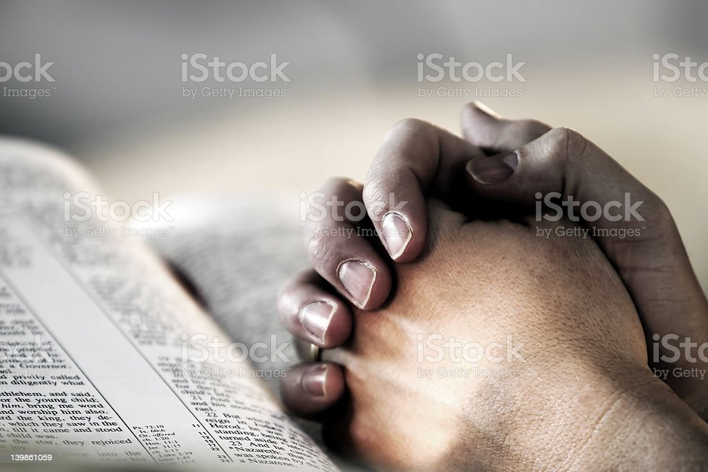 Praying Hands over a Holy Bible royalty-free stock photo