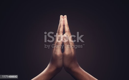 Praying hands with faith in religion and belief in God on dark background. Power of hope or love and devotion. Namaste or Namaskar hands gesture.