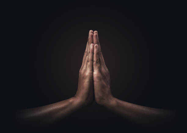 Praying hands with faith in religion and belief in God on dark background. Power of hope or love and devotion. Namaste or Namaskar hands gesture. Prayer position. stock photo