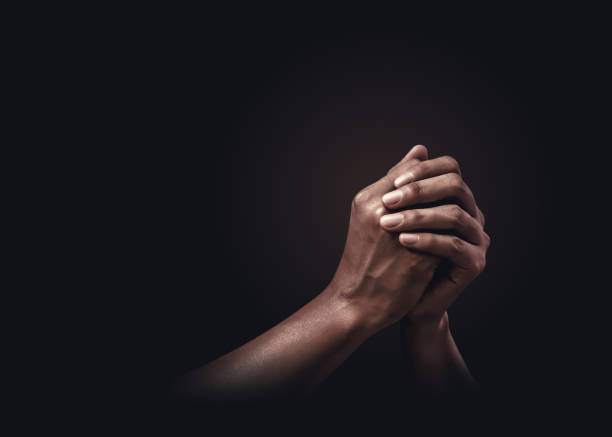 Praying hands with faith in religion and belief in God on dark background. Power of hope or love and devotion. stock photo