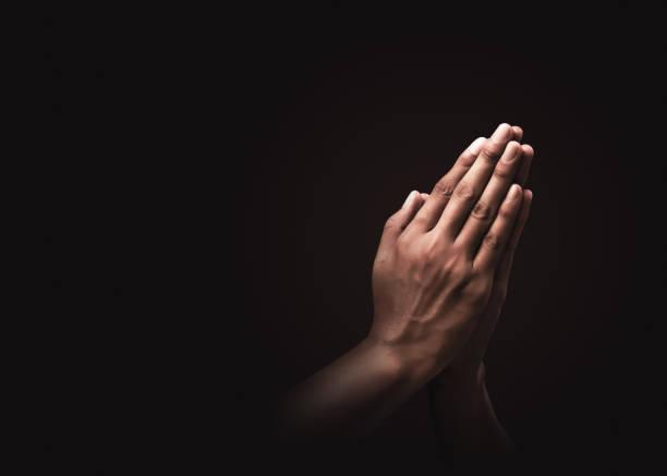 在黑暗的背景中,用對宗教和信仰的雙手祈禱。希望、愛和奉獻的力量。納馬斯特或納馬斯卡手手勢。禱告位置。 - prayer 個照片及圖片檔