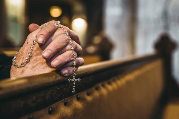 Praying hands with rosary in church stock photo