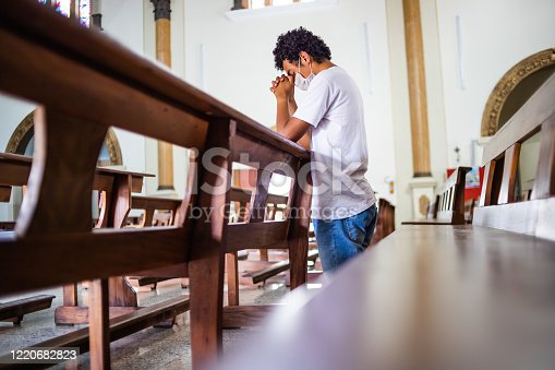 Young man, wearing a white protective mask, inside the church, praying in times of coronavirus