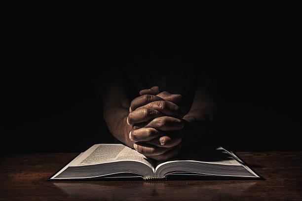 Praying in the dark stock photo